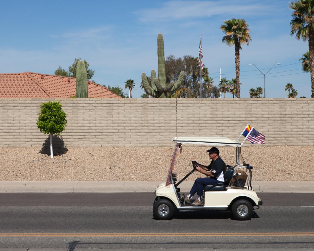 Voiturette de golf roulant sur une artère de la ville, Sun City West